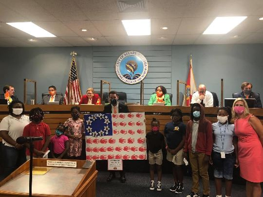 photo of students in front of city commission with art project of american flag